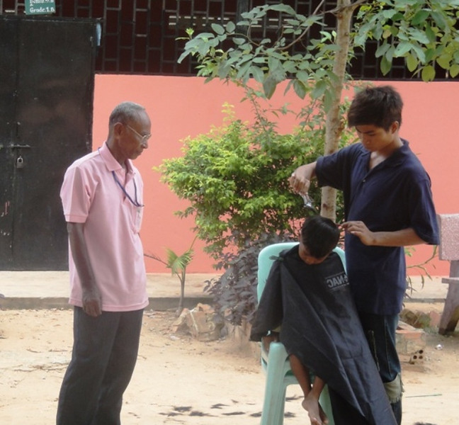 Village Elder, Soeum, oversees barbering operations for some of our students.